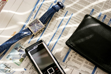 mobile, wallet and wrist watch on stocks page
