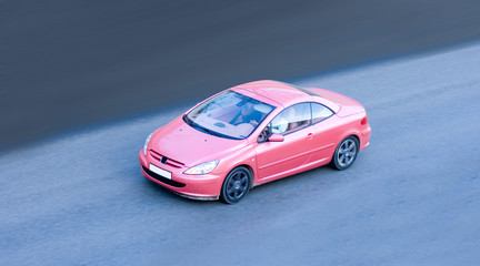 Fotobehang Snelle auto s woman driving small pink coupe car fast speed