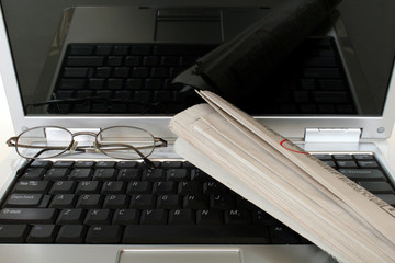 laptop with newspaper and eyeglasses