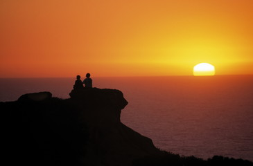 couple in silhouette on rock at sunset, torrey pin