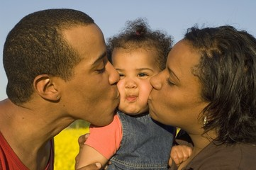 parents kissing their cute little baby