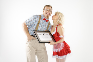 young man receiving kiss and certificate from young woman.