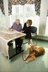 two women petting dog and doing jigsaw puzzle.