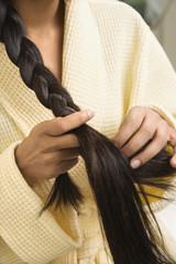 Young woman braiding hair.