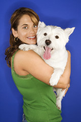 Woman holding white terrier dog.