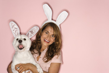 Woman and white dog wearing rabbit ears.