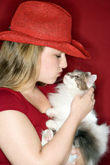 Caucasian female holding and kissing cat.