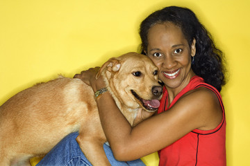 Adult female petting dog.