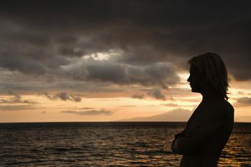 Teen boy looking at Maui Hawaii ocean.