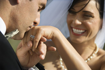 Groom kissing hand of smiling bride.