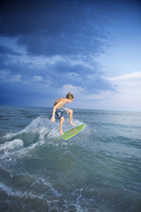 Male teen riding skimboard.