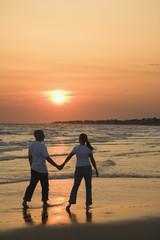 Couple on beach at sunsest.