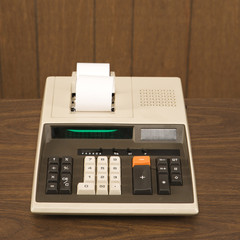 still life shot of a vintage calculator sitting on a wooden desk