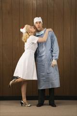 female nurse kissing surgeon on cheek.