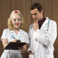 nurse and doctor looking at clipboard.