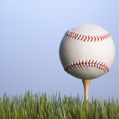 baseball resting on golf tee in grass.