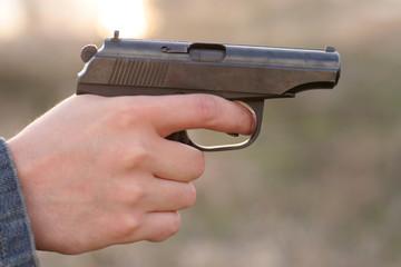 man's hand and a gun