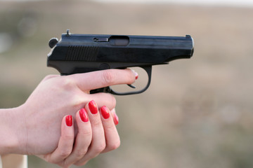 woman's hand and a gun
