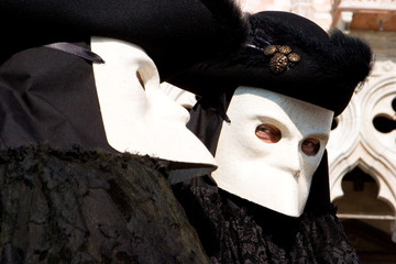two venetians in black costumes and white masks