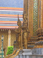 wat phra kaeo and the grand palace in gold with warrior statues,
