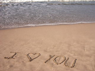 i love you written on sandy beach