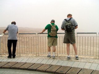 tourists looking at mountains of sand in massada