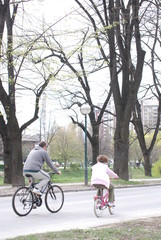 father and daughter riding bike in park