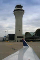 air traffic control tower with the wing of the plane