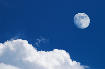 white clouds and full moon over deep blue sky