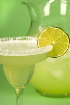 close up of margarita with a pitcher of margaritas