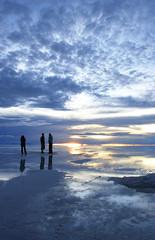 group watching sunset over wet salt flats