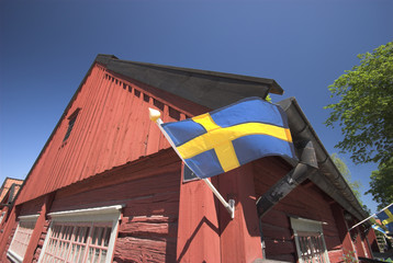 swedish flag and red  wooden house