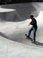 Skate boarder speeding up a bowl in a skatepark