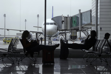 Passengers in an airport terminal with a plane in background.