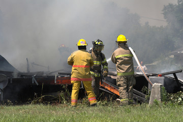 Fire fighters look for victims in debree of burned out home