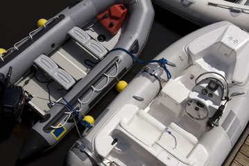 Three inflatable boats tied together in a dock.