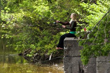 Pretty blond, barefoot woman fishing