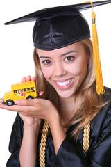 A pretty woman graduate holding a school bus