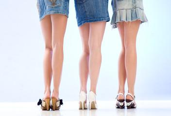 Beine und Pos von drei Mädchen im Minirock