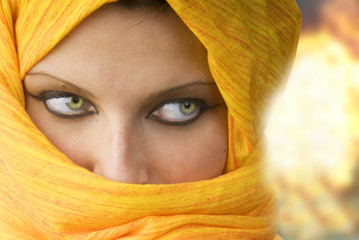 attactive and strong eyes behind an orange scarf