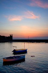 Beautiful sunset at a marina with small boats in the foreground