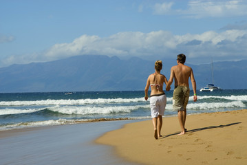 young couple walks along the beach in Hawaii