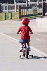 Boy in red riding his bike