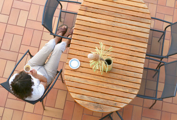 Young girl sitting on the terrace drinking coffee