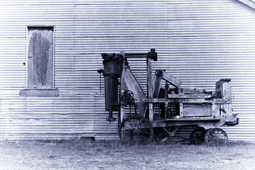 an old wool baler in front of a barn in purple toning