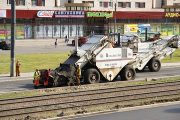 People work on an asphalt spreader