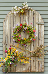 Weather beaten wooden planks with vines and flowers on a wall