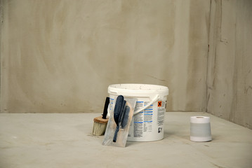 white bucket with trowel and paint brush