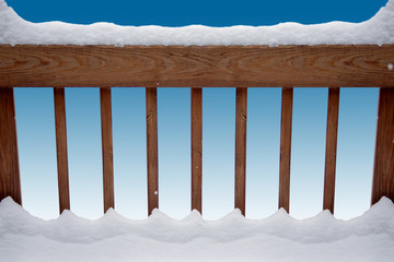 snow gracing a deck railing over a blue background