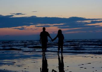 Couple near sea at sunset.